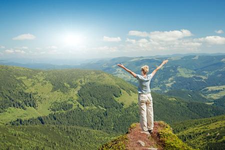 幸せな年配の女性の上げられた手を空にして山で自然を満喫します。自由の概念