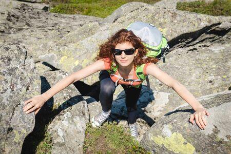 escalando: Caminante con mochila de escalada en la roca