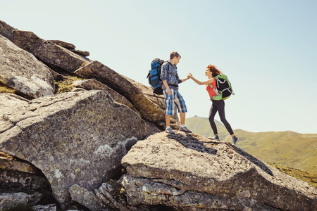 Hiker couple helps each other to climb on the rock in mountains Imagens
