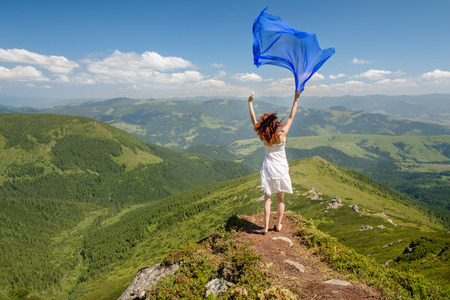 Gelukkige vrouw genieten van de natuur in de bergen met blauwe weefsel in handen op blauwe hemel achtergrond