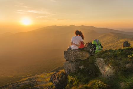 Gelukkig paar voelen vrijheid en genieten van het prachtige uitzicht op de bergen en op zoek op de zonsondergang