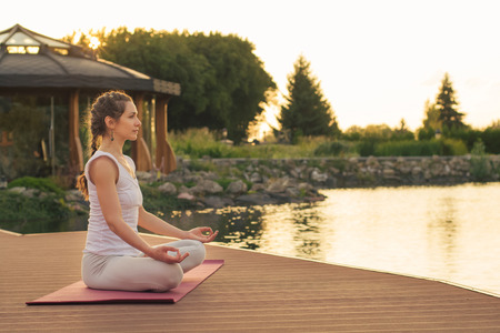 Woman meditating near lake on sunset Stock Photo