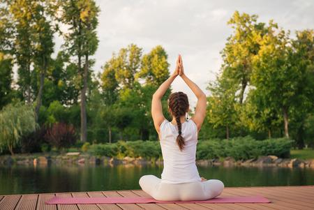relaxation exercise: Woman doing yoga exercises near lake on sunset