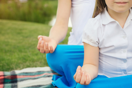 Young mother and daughter meditating and doing yoga exercise on the nature
