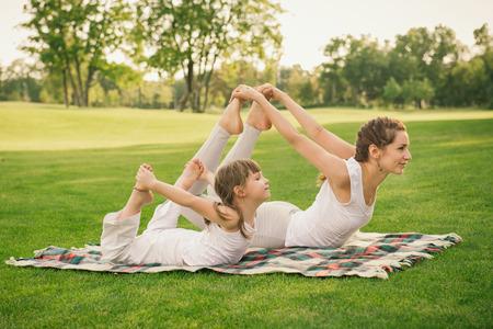 gimnasia: Joven madre y su hija haciendo gimnasia y estiramientos en el parque de la ciudad en la puesta del sol