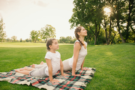 teach: Mother and daughter doing exercise outdoors. Family healthy lifestyle concept. Stock Photo