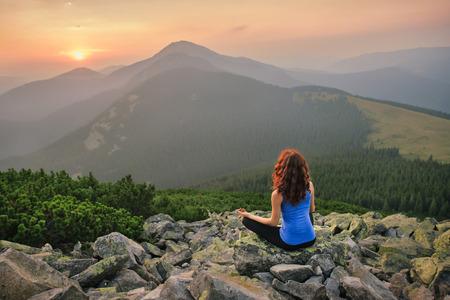 Vrouw voelt vrijheid en genieten van het prachtige uitzicht op de bergen en op zoek op zonsondergang