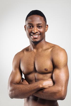 Positieve Afro-Amerikaanse gespierde man met handen gekruist op een grijze achtergrond Stockfoto
