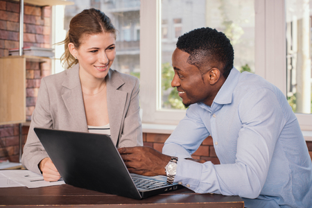 young: Businessman and businesswoman having meeting in office. Young business people discussing something while looking at the computer monitor together Stock Photo