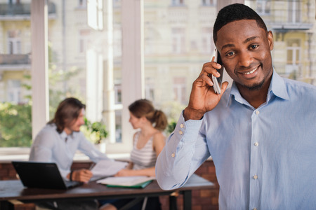 telephone interview: Confident african american man in formal wear waiting for job interview and talking on mobile phone Stock Photo
