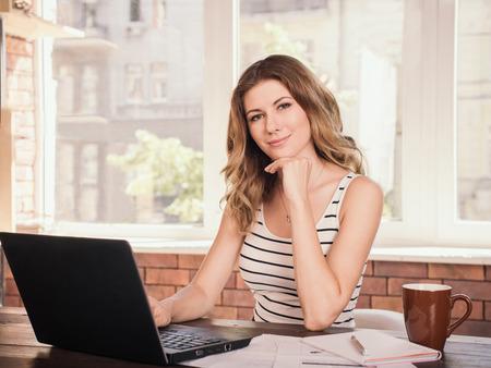 Portret van een mooie zakelijke vrouw glimlacht en zitten in de buurt tafel scherm