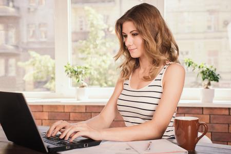 Close-up portret van een mooie jonge vrouw glimlacht en kijken naar laptop scherm
