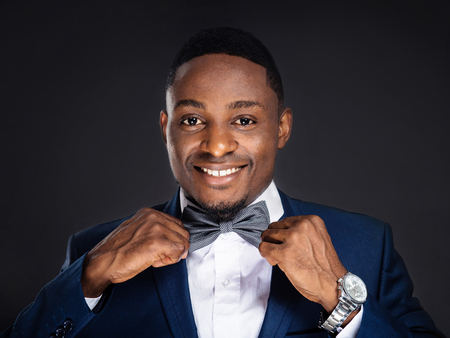 african business: Handsome african american stylish man with bow tie on black background Stock Photo