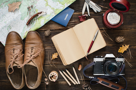 Top view of modern collection for travel on wooden background. Autumn mood concept
