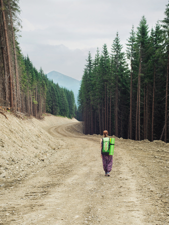 walking alone: Young woman with backpack walking alone on the mountain road