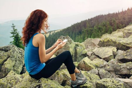 lady on phone: Woman hiker enjoying nature use her smartphone on the mountain peak at sunset