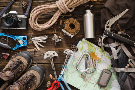 Equipment necessary for mountaineering and hiking on wooden background Standard-Bild
