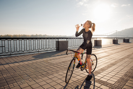 Sport woman drinking water after riding a bicycle in the morning city