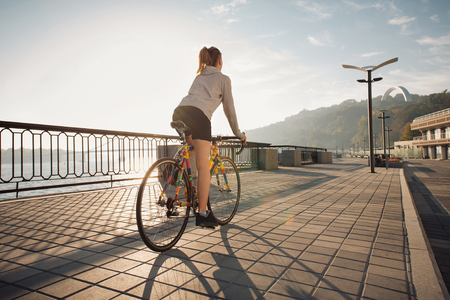 Jonge vrouw rijdt op een fiets in de ochtend de stad bij zonsopgang
