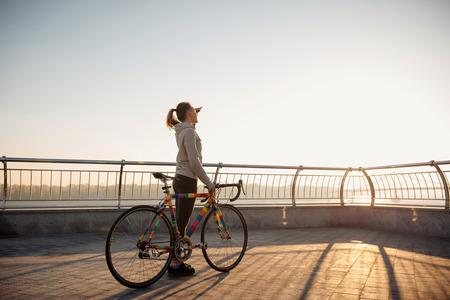 bicicleta: Mujer joven que monta una bicicleta en la ciudad por la mañana al salir el sol