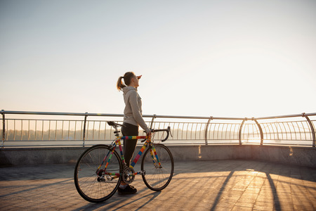 road cycling: Young woman riding a bicycle in the morning city at sunrise Stock Photo