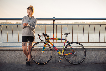 extreme: Young tattooed woman standing near bicycle and using smartphone