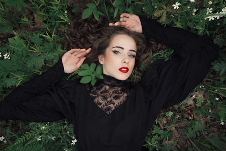 medieval dress: Beautiful woman lying down on green grass in medieval dress