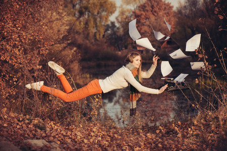 levitacion: Woman writer levitation in the autumn forest near lake. Concept of freedom and independence in the work