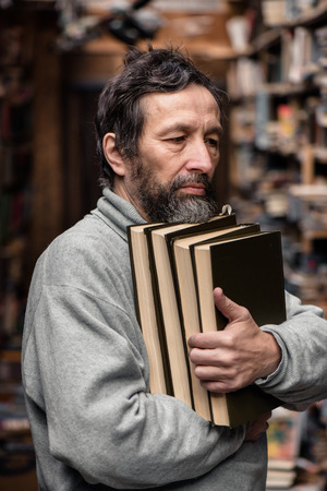 Portrait of authentic senior man with beard and good eyes holding books in the hand on book market background