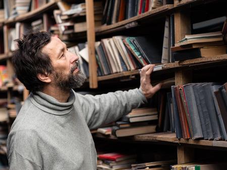 Portret van de authentieke senior man met baard en snor op boekenmarkt