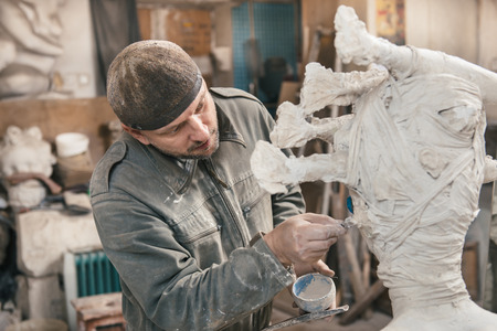 Sculptor man сreating sculpture from plaster and clay in his workshop