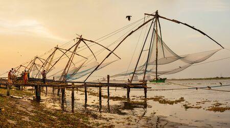 net: People walking near chinese fishing nets on sunset background  in Cochin Kochi, Kerala, India Stock Photo