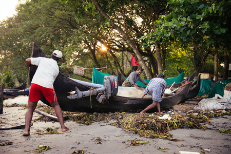 kochi: Kochi, India - November 29, 2015: Indian fishermen after fishing in their wooden boats in the early morning on the sea beach in Fort Kochi Cochin, Kerala, India.