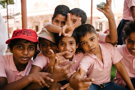 pobre: Kochi, India - 28 de noviembre de 2015: los niños indios juguetones tener descanso y sonriente en la calle después de la escuela en Fort Kochi Cochin, Kerala, India.
