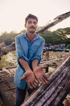 kochi: Kochi, India - November 29, 2015: Traditional technology of fishing. Fisherman shows damaged hands after hardly working on Chinese fishing net on the sea beach in Fort Kochi Cochin, Kerala, India.