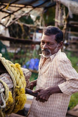 hardly: Kochi, India - November 29, 2015: Traditional technology of fishing. Fisherman hardly working on Chinese fishing net on the sea beach in Fort Kochi Cochin, Kerala, India.