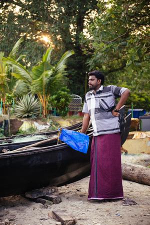 kochi: Kochi, India - November 29, 2015: Portrait of indian fisherman standing near boat on the sea beach in Fort Kochi Cochin, Kerala, India.