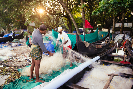 india fisherman: Kochi, India - November 29, 2015: Indian fishermen after fishing in their wooden boats in the early morning on the sea beach in Fort Kochi Cochin, Kerala, India.