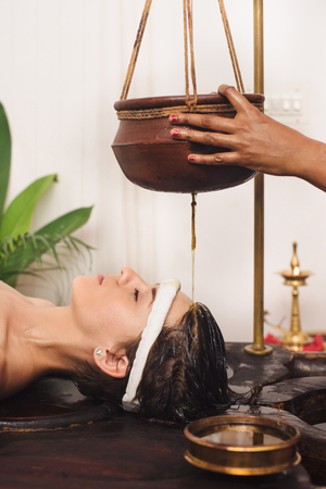 kerala: Caucasian woman having Ayurveda shirodhara treatment in India Stock Photo