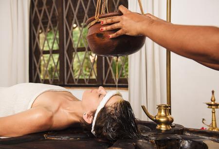 Blanke vrouw die Ayurveda shirodhara behandeling in India