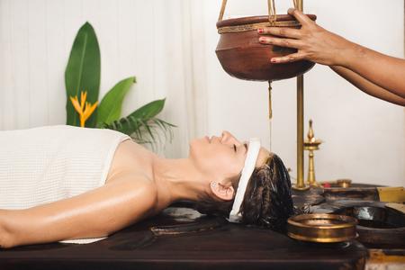 masaje: La mujer caucásica que tiene un tratamiento shirodhara Ayurveda en la India Foto de archivo