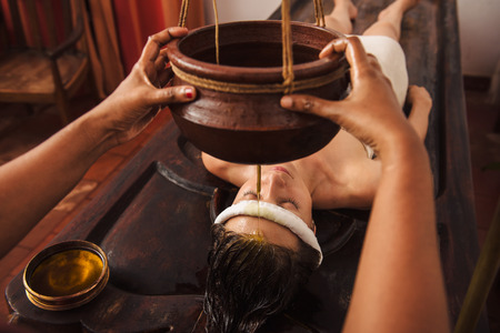 the caucasian beauty: Caucasian woman having Ayurveda shirodhara treatment in India Stock Photo