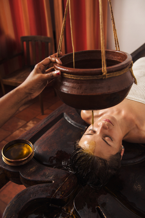 Caucasian woman having Ayurveda shirodhara treatment in India Imagens