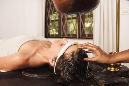 Caucasian woman having Ayurveda shirodhara treatment in India Stock Photo