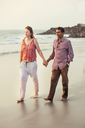 multiracial family: Happy mixed race couple holding by hand and walking on the beach at sunset. Stock Photo