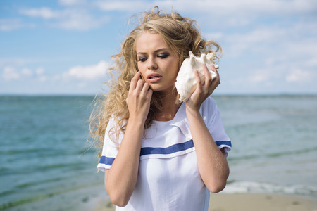 blue hair: Beautiful blond woman in sea style dress standing near the beach and enjoying sea sound from shell Stock Photo