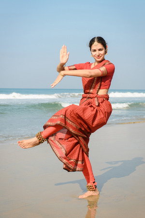 Beautiful indian woman dancer shiva dance in traditional clothing near the beach