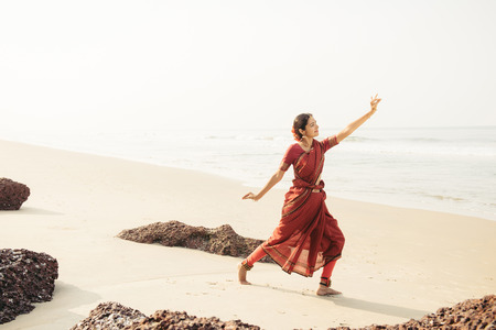 bharatanatyam: Beautiful indian woman dancer in traditional clothing near the beach Stock Photo