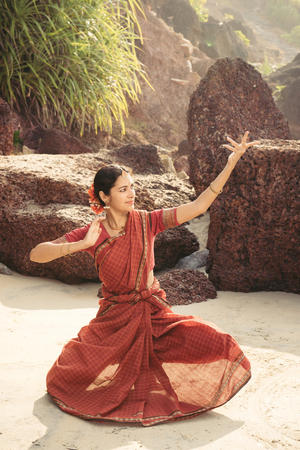Indian classical dance Bharatanatyam performed by beautiful woman in traditional clothing