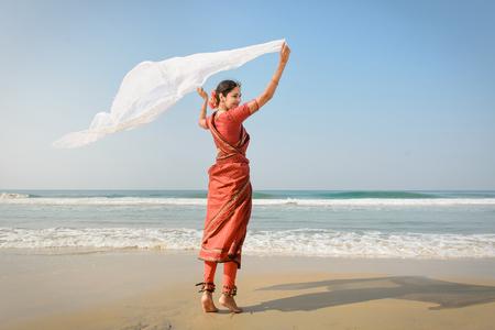 cheerful woman: mujer india sentir la libertad y de pie cerca de la playa en la ropa sari tradicional con tejido blanco en las manos Foto de archivo